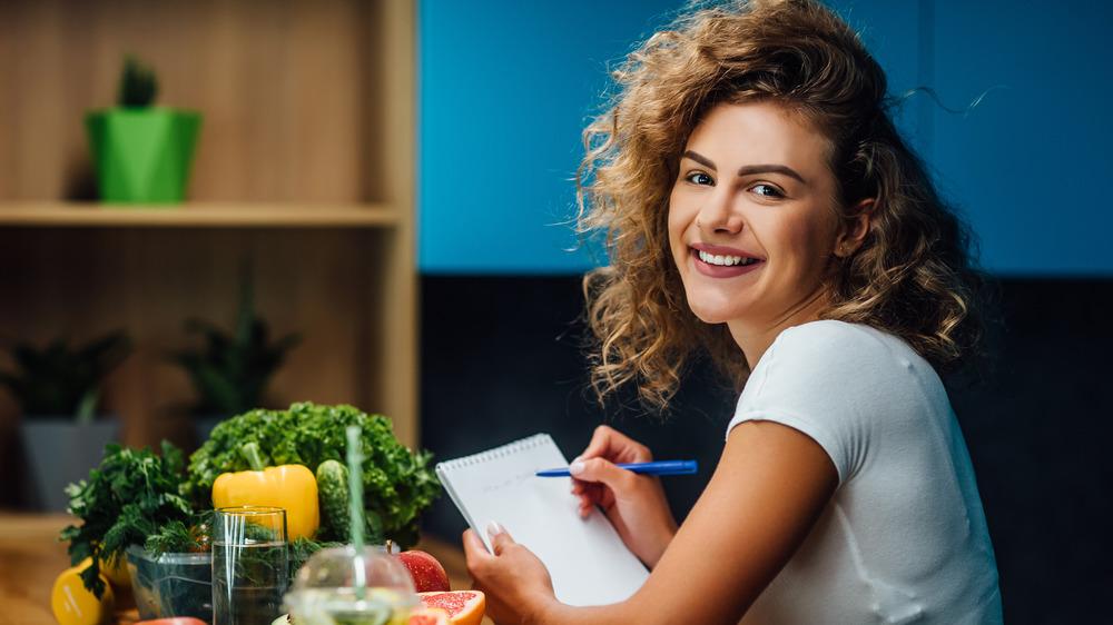 smiling woman beside vegetables