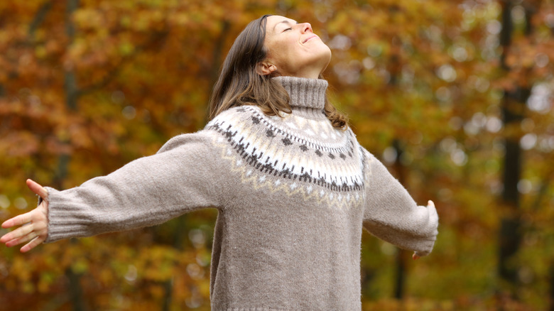 woman with outstretched arms and autumn leaves