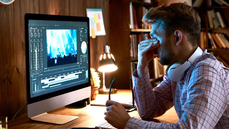 Man rubs his eyes while at a computer