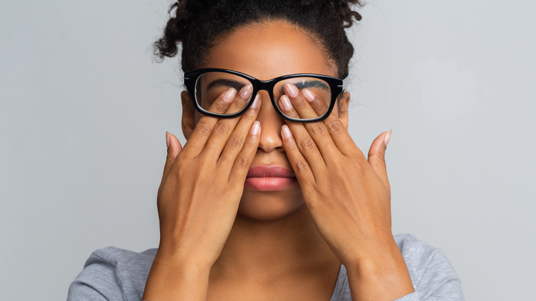 A woman with glasses rubs her eyes