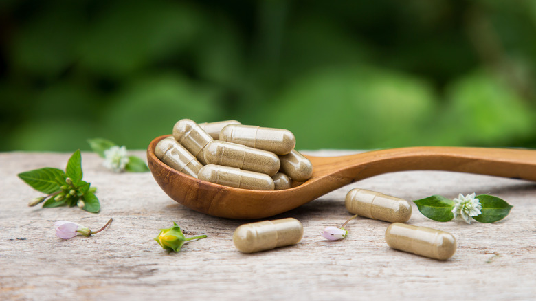herbal supplements on wooden spoon