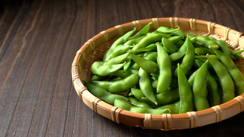A bowl of edamame sits on a table