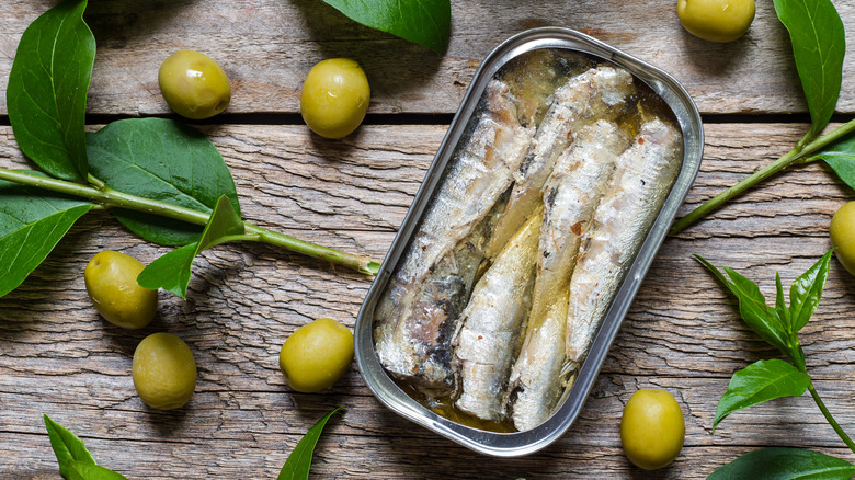 A can of sardines on a rustic table