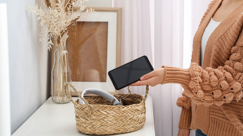 Woman putting smartphone into wicker basket with gadgets at home.