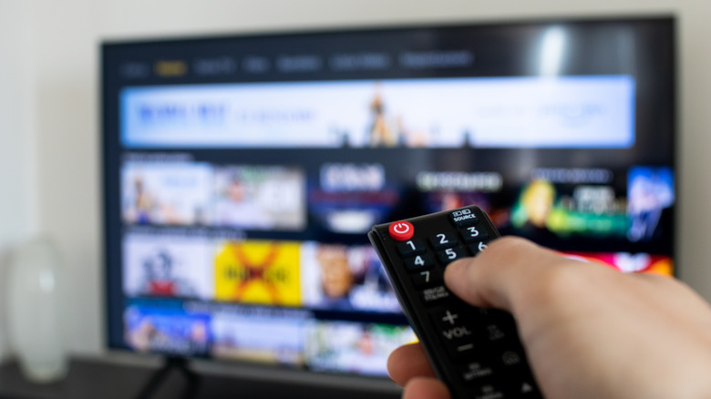 Someone points a remote at a TV