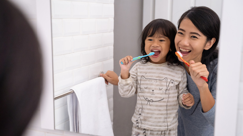 mom and daughter brushing their teeth while looking in the mirror