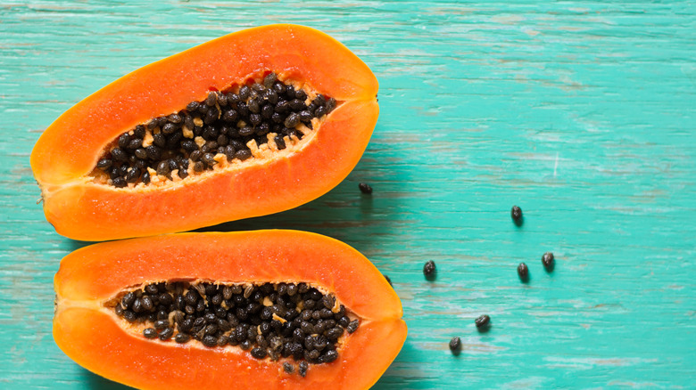 Two papaya halves on a wooden table