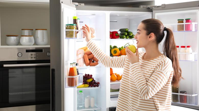 A woman eats an apple near the fridge