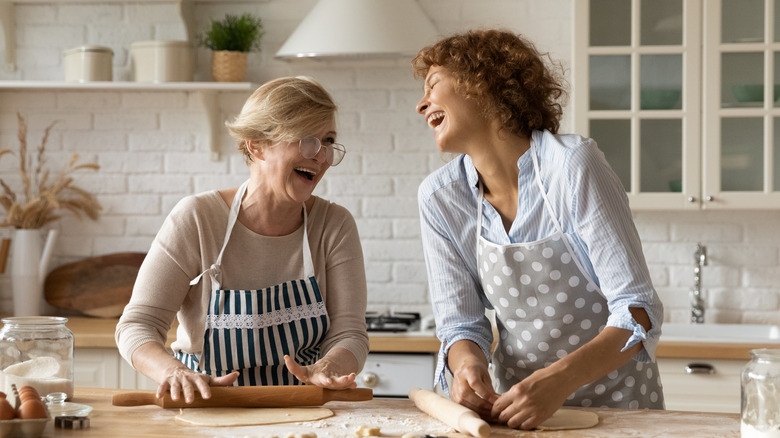 women laughing while baking in a kitchen