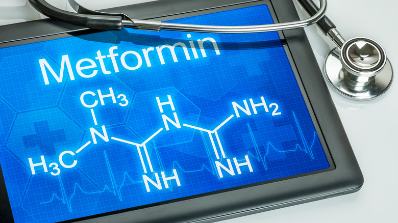 Tablet with chemical formula of metformin with stethoscope laying on it