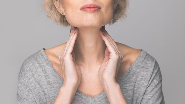 Woman touching thyroid gland
