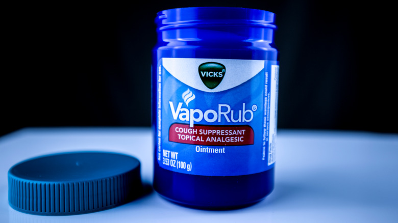 A blue jar of open Vicks with a black background