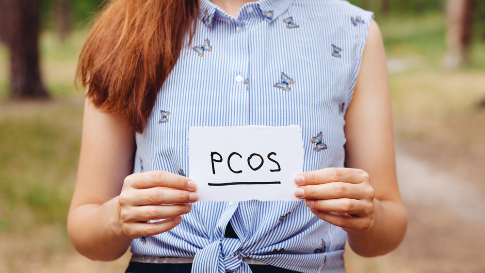 PCOS written on paper held up by woman
