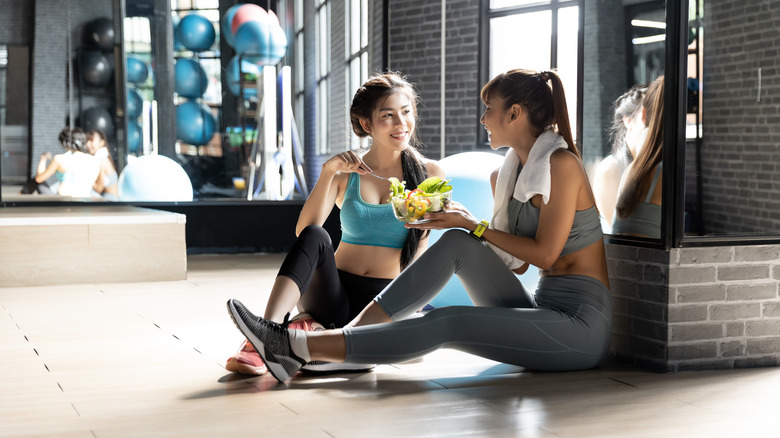 Two girls eat after a workout