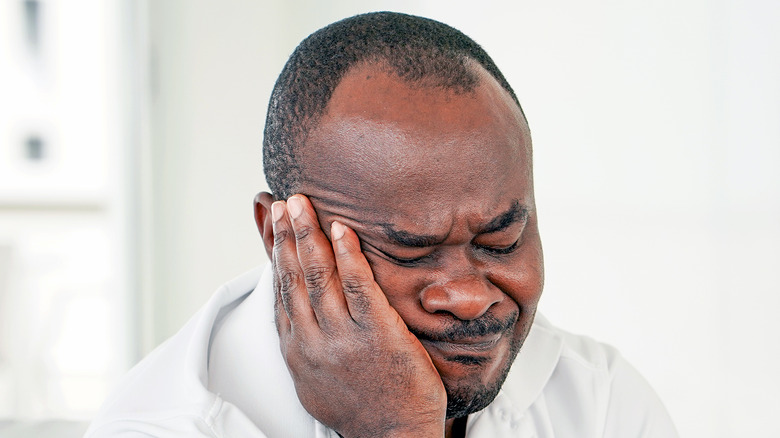depressed man holding his face