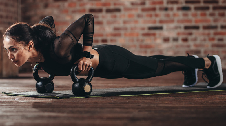 Fit woman doing kettlebell push-ups