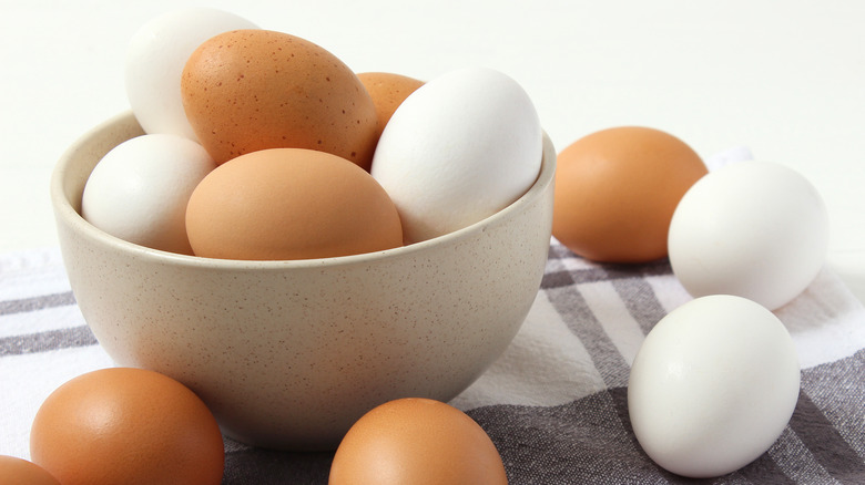 white and brown eggs in a bowl