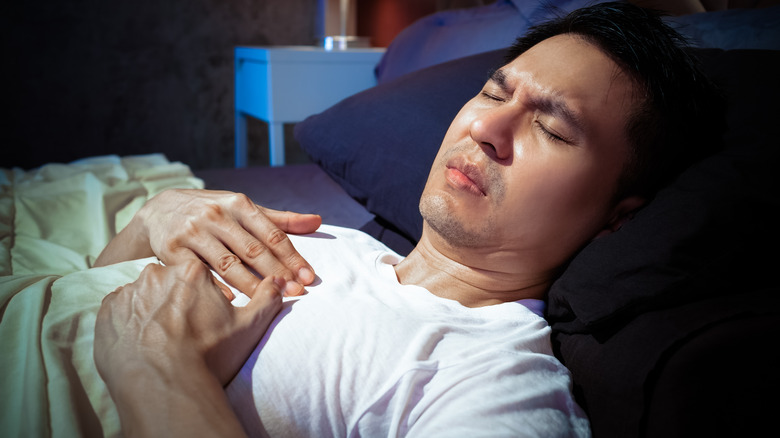 man in bed with chest pain
