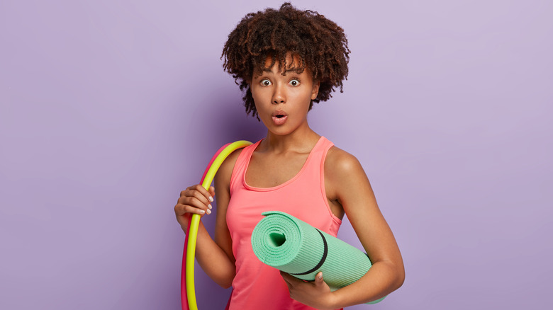 Black woman with exercise gear looking surprised