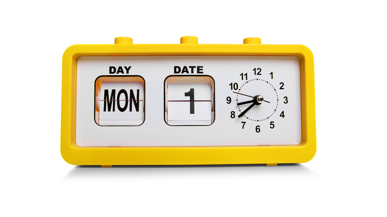 a yellow digital clock showing both the date and the time