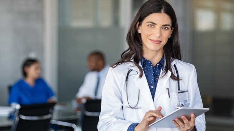 Portrait of a woman with white coat and stethoscope holding a tablet. Two people are talking in the background.