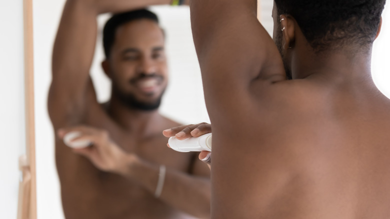 Man applying deodorant while looking in the mirror