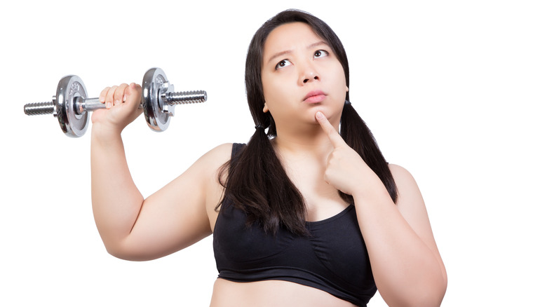 confused-looking woman holds dumbbell