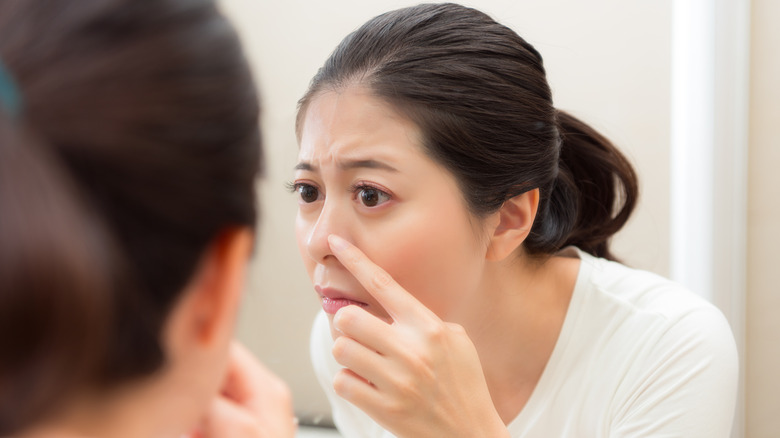 Woman looking at blackheads in mirror