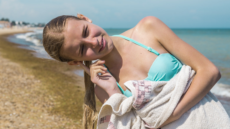 Girl at the beach removing water from her ear