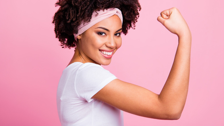 A smiling woman doing an arm curl to show off a toned tricep