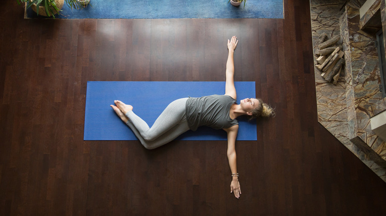 A woman performs a spinal twist yoga position