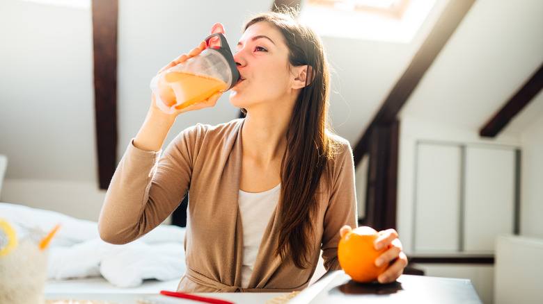 A woman drinks an orange drink at home
