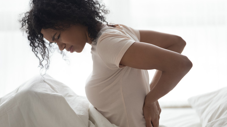 A young woman rubbing her back in back pain