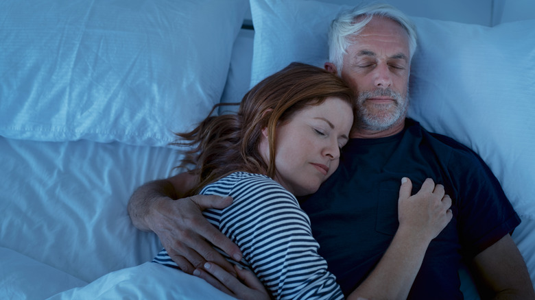 Couple asleep in bed together