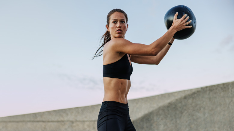 Fit woman holding up a medicine ball