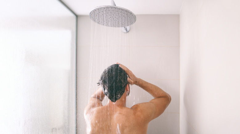 Man showering and rinsing hair
