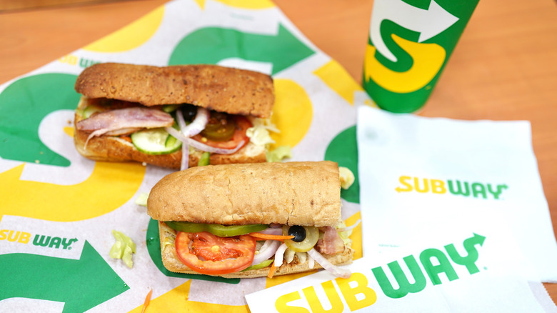 two Subway sandwich's lying on Subway paper with a fountain drink