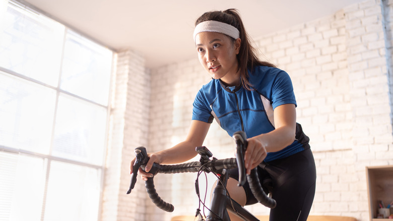 young woman looking intense while on a stationary bike