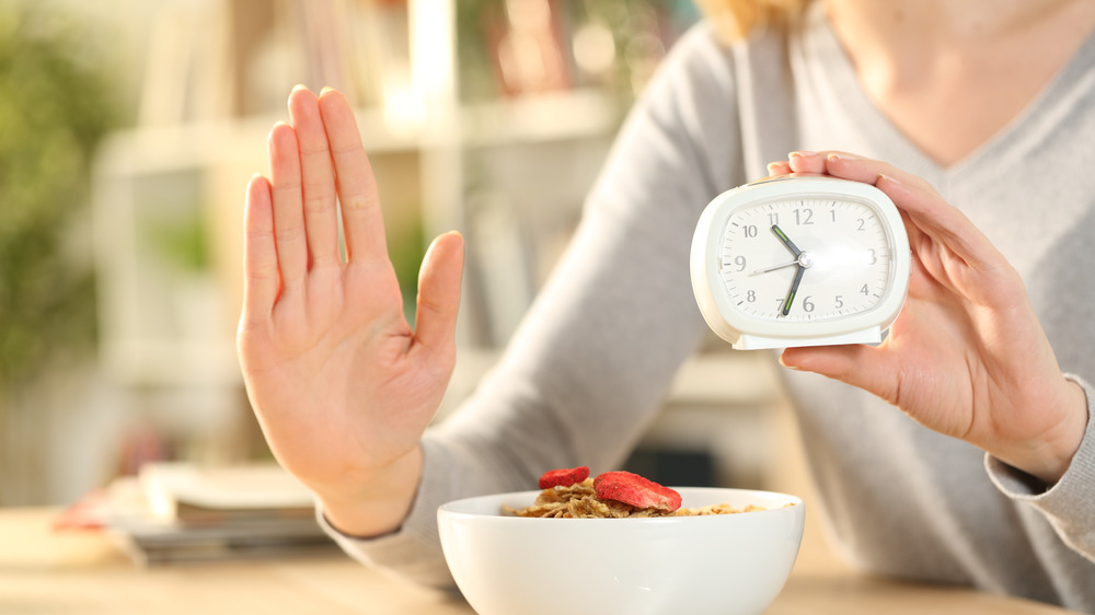 Woman holding clock denying food