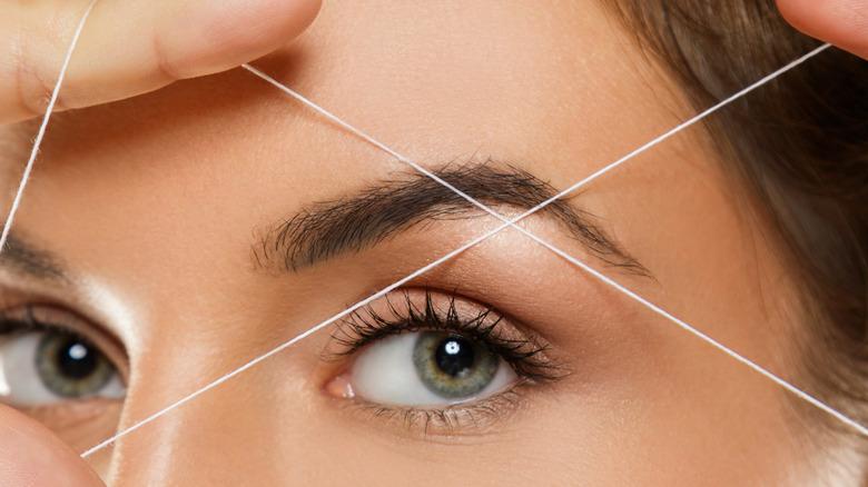young female holding up eyebrow threads around her eye region