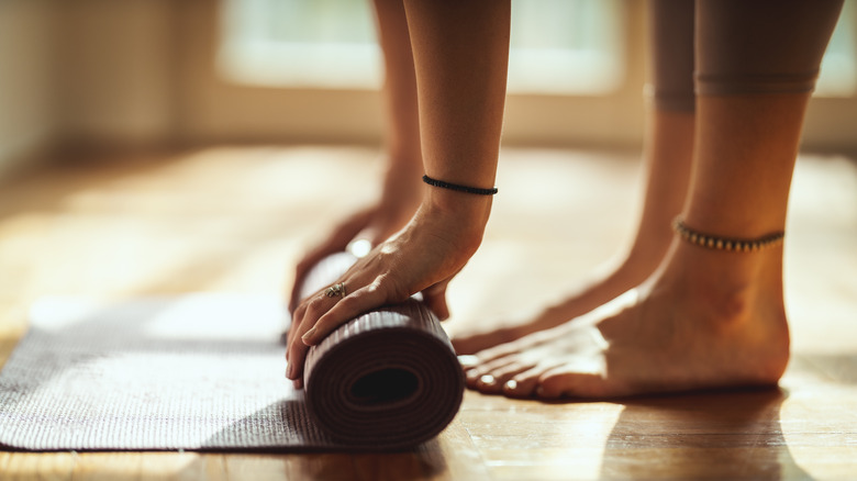 Close-up of a woman's hands rolling up exercise mat