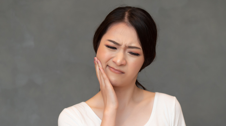 A woman has a toothache on the side of her face