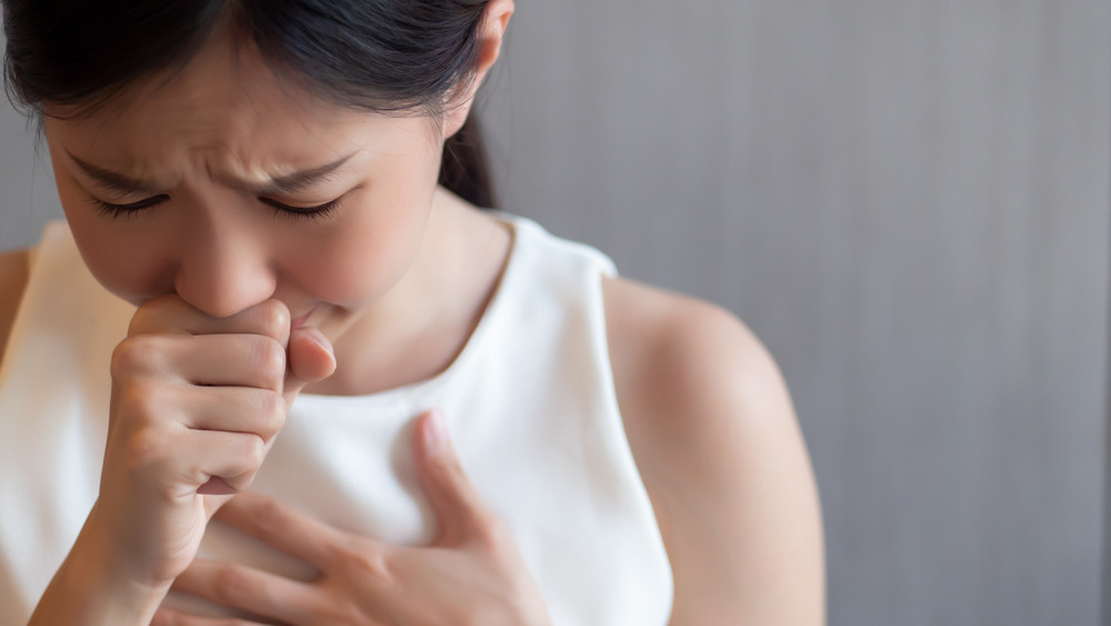 Young woman holding throat choking