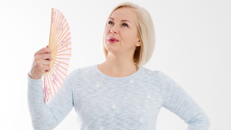 Woman in gray sweater holding a hand fan to cool off