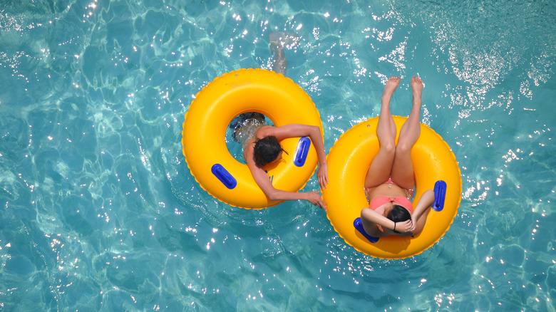 women floating on tubes in pool