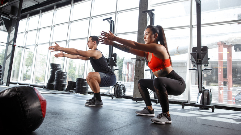 Two people doing squats in a gym
