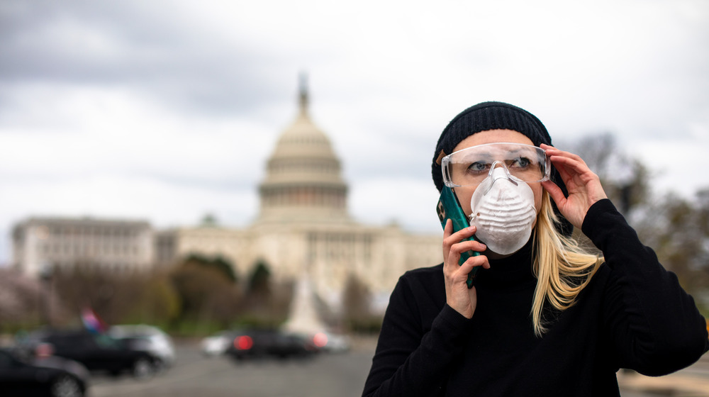 Woman in mask stands in front of US Capitol