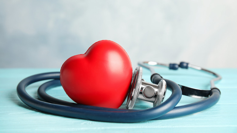 Red heart toy sitting inside a coiled up stethoscope