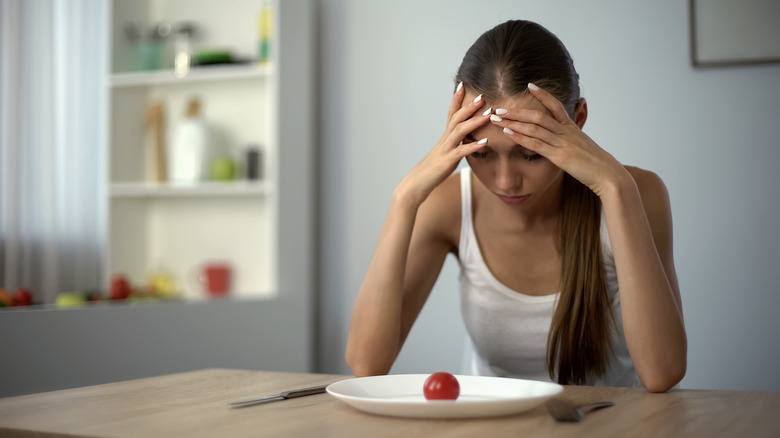 Girl stares at a plate with one tomato on it hungry