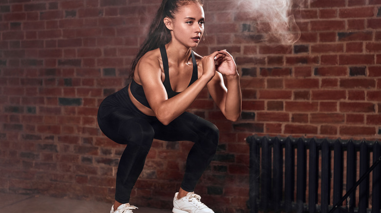 woman squatting in front of brick wall